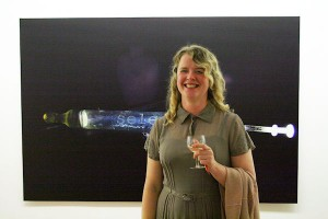 Fiona O'Dwyer standing in front of her piece called 'Select', photographic paper on aluminium (65 x 43 inches).