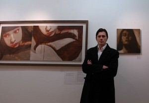 Artist Darko at The Lyndsay Gallery Monkstown in front of his paintings