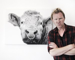 Jason Byrne next to one of Kelly Hood's Cow Paintings.
