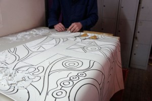 Artist cutting one of the lino tiles.