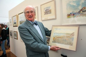 Artist Thomas Wilson with one of his paintings at the exhibition opening