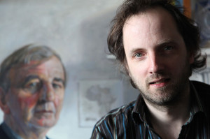 Artist Oisin Roche with his portrait of Niall Andrews in the back ground (Photo Liam Madden)