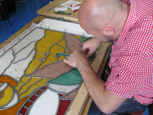 Working on a stained glass window.